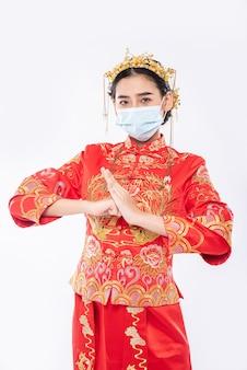 Vrouw draagt cheongsam-pak en masker welkom klant om te winkelen in chinees nieuwjaar
