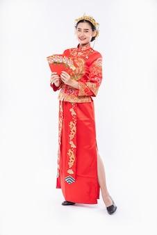 Vrouw draagt cheongsam-pak en zwarte schoen blij met het krijgen van cadeaugeld van de baas in chinees nieuwjaar