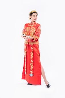 Vrouw draagt cheongsam-pak en zwarte schoen klaar om het geschenkgeld aan familielid te geven