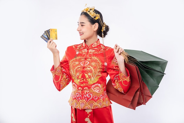 Vrouw draagt cheongsam-pak, gebruikt creditcard om te winkelen, veel winkelen in chinees nieuwjaar