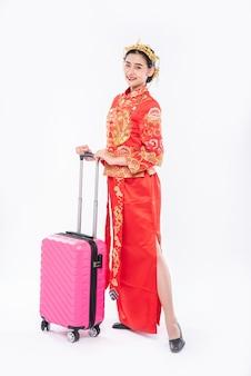 Vrouw draagt cheongsam-pak, gebruikt roze reizigerstas voor reis in chinees nieuwjaar