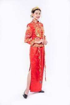 Vrouw draagt cheongsam pak glimlach om reiziger te verwelkomen die in chinees nieuwjaar winkelt