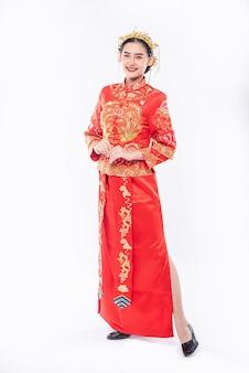 Vrouw draagt cheongsam-pak glimlach om reiziger te verwelkomen op evenement in chinees nieuwjaar
