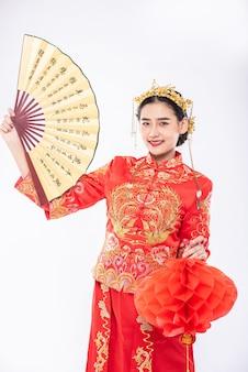Vrouw draagt cheongsam-pak houdt de chinese handventilator en rode lamp vast om te laten zien op een groot evenement in chinees nieuwjaar