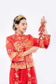 Vrouw draagt cheongsam-pak met glimlach om vuurwerk van de baas te krijgen in chinees nieuwjaar
