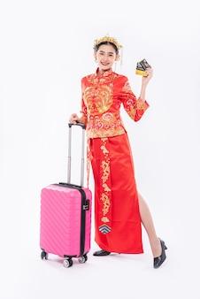 Vrouw draagt cheongsam-pak met kroon, bereidt roze reizigerstas en creditcard voor op reis in chinees nieuwjaar