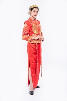 Vrouw draagt cheongsam-pak promoot om reizigers te verwelkomen die winkelen in chinees nieuwjaar