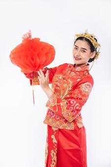 Vrouw draagt cheongsam-pak promoot rode lamp naar klant in chinees nieuwjaar