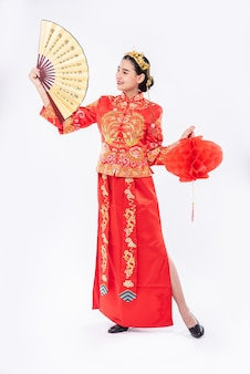 Vrouw draagt cheongsam-pak ter promotie van de chinese handventilator en rode lamp op een groot evenement in chinees nieuwjaar