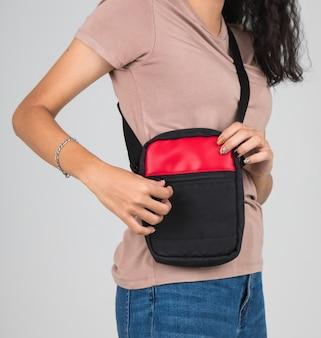 Vrouw draagt de casual tas op de schouder met een actief en gemakkelijk gebaar.