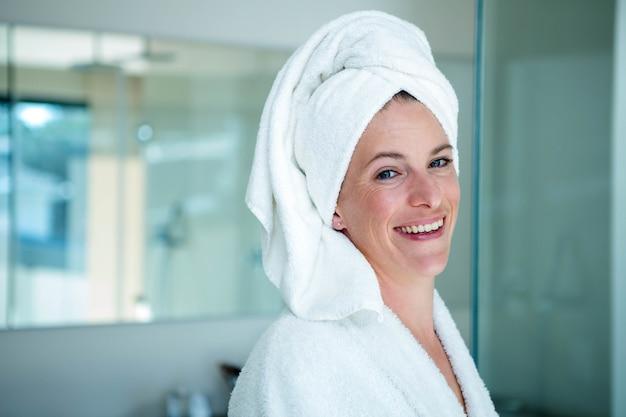 Vrouw draagt een badjas en een handdoek op haar hoofd lacht
