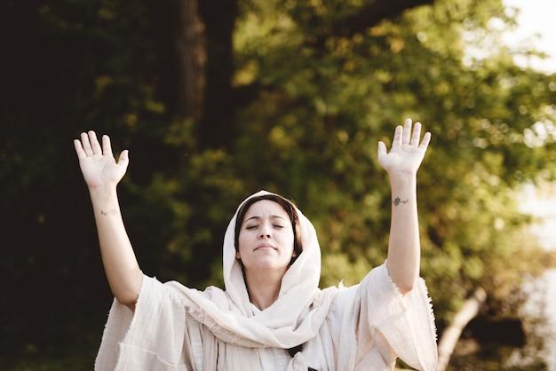 Vrouw draagt een bijbelse jurk met haar handen omhoog naar de hemel