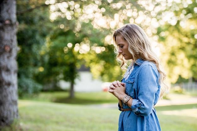 Vrouw draagt een blauwe jurk en bidt in een tuin onder zonlicht