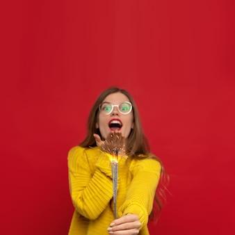 Vrouw draagt een bril en een gele trui met wonderkaarsen en een kus waait