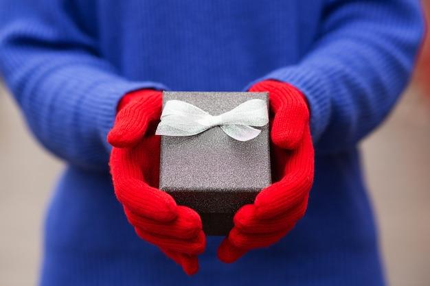 Vrouw draagt een diepblauwe trui en rode winterhandschoenen met een kleine geschenkdoos met een strik