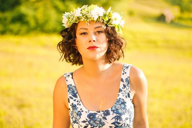 Vrouw draagt een gebloemde jurk met een bloemenkrans op haar hoofd en poseert in een veld