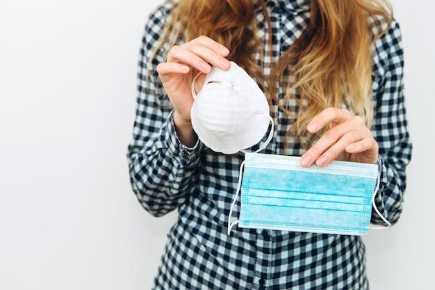 Vrouw draagt een gezichtsmasker op een witte achtergrond. beschermende medicijnen tegen coronavirus. de covid 2019-epidemie. Premium Foto