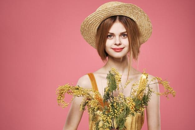Vrouw draagt een hoed boeket van mimosa bloemen roze levensstijl.