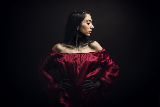 Vrouw draagt een rode jurk en een enge make-up op haar gezicht en dient voor een zwarte achtergrond in