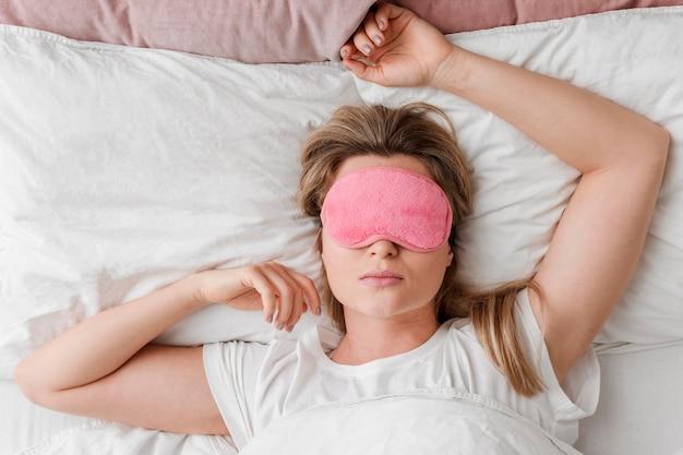 Vrouw draagt een slaapmasker op haar ogen