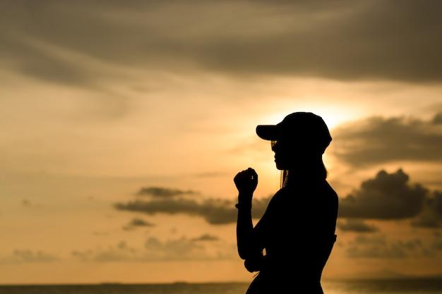 Vrouw draagt een zonnebril en pet met zonsondergangsilhouet