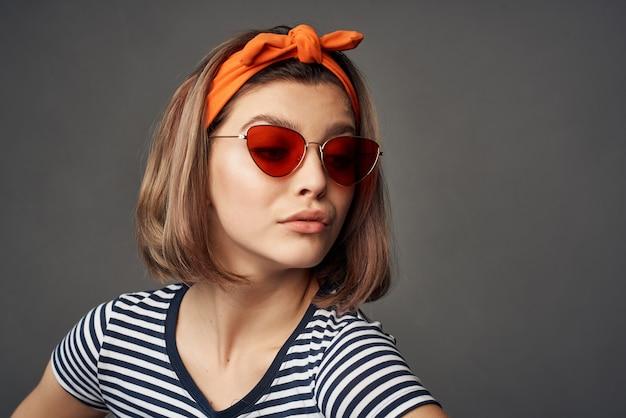 Vrouw draagt een zonnebril in een gestreept t-shirt met een verband op zijn hoofd poseren mode. hoge kwaliteit foto
