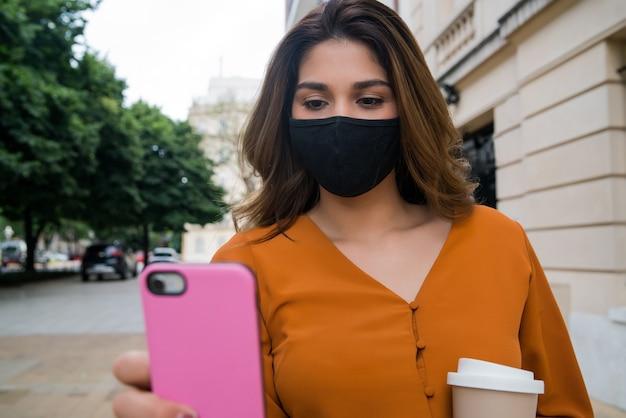 Vrouw draagt gezichtsmasker en gebruikt haar mobiele telefoon terwijl ze buiten op straat staat. nieuw normaal levensstijlconcept.