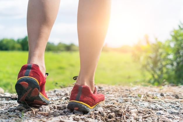 Vrouw draagt hardloopschoen om te wandelen en rennen op de groene achtergrond van de natuur. gezondheidsoefening concept.