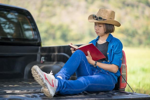 Vrouw draagt hoed en het lezen van het boek op pick-up truck