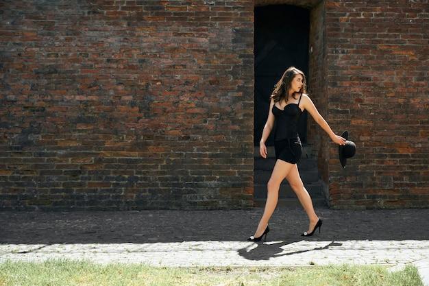 Vrouw draagt jurk wandelen in de buurt van oude bakstenen muur.