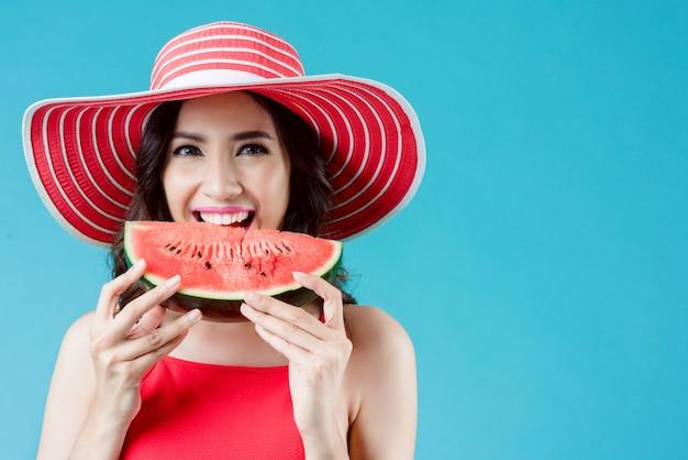 Vrouw draagt jurk. ze is watermeloen aan het eten. in de zomer voelt ze zich fris