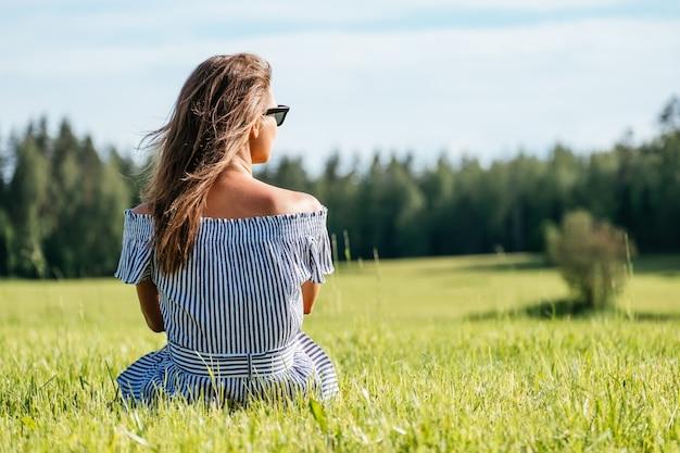 Vrouw draagt jurk zittend op groen grasveld, zomerseizoen, ontspanning op het platteland, genieten van de natuur, plezier concept