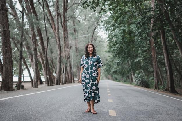 Vrouw draagt mooie lange jurk staande op de weg onder groene bomen.
