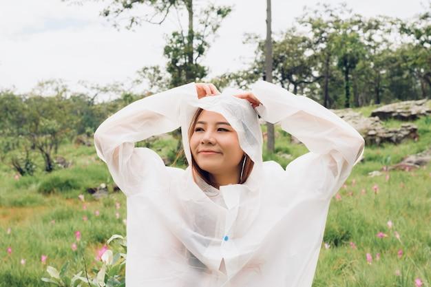 Vrouw draagt regenjas staan in het regenwoud