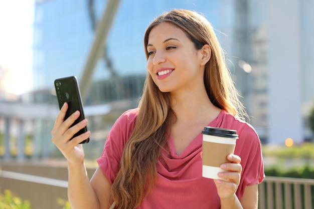 Vrouw draagt ?? roze blouse videobellen met smartphone buitenshuis