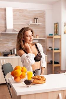 Vrouw draagt sexy lingerie ontspannen in de keuken van het huis na het bereiden van een heerlijk ontbijt. jonge aantrekkelijke vrouw met tatoeages in verleidelijk ondergoed met kopje thee ontspannen in de keuken glimlachend.