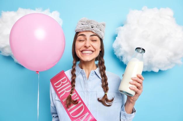 Vrouw draagt slaapmasker op hoofd houdt glazen fles melk vast en ballon geniet van gezellige huiselijke sfeer modellen tegen blauw