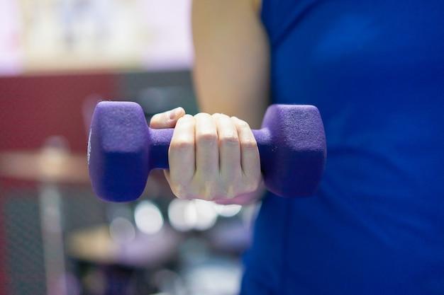 Vrouw draagt sporthorloge houdt halter opheffend met één hand kracht lip voor borst biceps spier krachttraining indoor onscherpe achtergrond