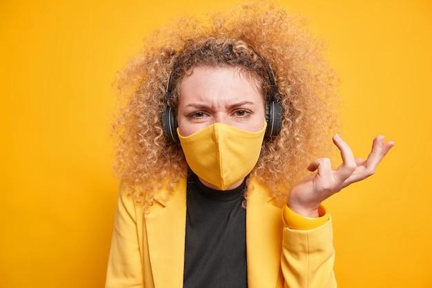 Vrouw draagt stereo koptelefoon om naar muziek te luisteren beschermend gezichtsmasker tegen coronavirus steekt hand aarzelend op
