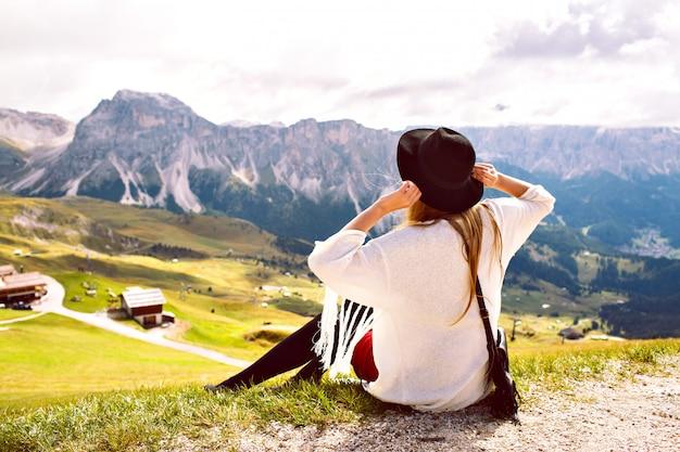 Vrouw draagt stijlvolle boho-outfit, loopt alleen en geniet van een adembenemend uitzicht op de oostenrijkse alpen