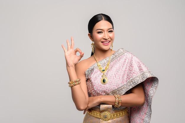 Vrouw draagt thaise kleding en hand symboliseert ok