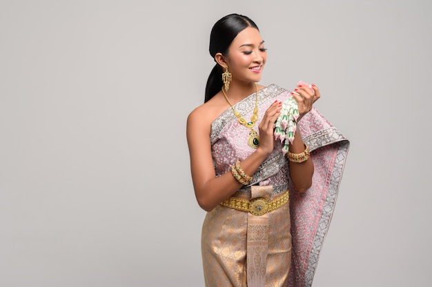 Vrouw draagt thaise kostuum en hand slingers van bloemen.