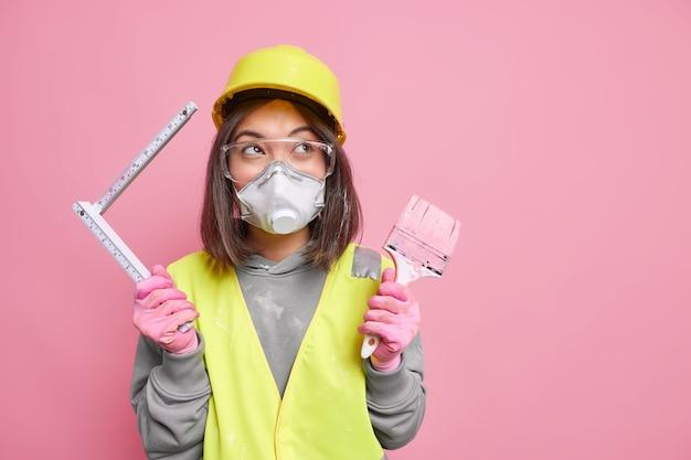 Vrouw draagt veiligheidsbril gasmasker en helm houdt schilderborstel meetlint reparaties appartement stands
