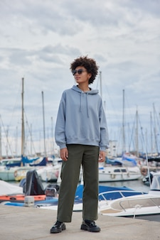 Vrouw draagt zonnebril hoodie en broek poseert op jachthaven geniet van vrije tijd bewondert prachtige uitzichten heeft promenade tijdens tijdverdrijf