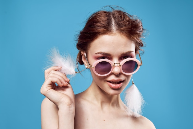 Vrouw draagt ?? zonnebril oorbellen luxe emoties close-up blauwe achtergrond. hoge kwaliteit foto
