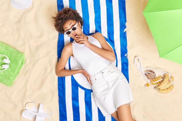 Vrouw draagt zonnebril witte kleren ligt op blauw gestreepte handdoek brengt vakantie door aan zee omringd door parasol zak fruit pantoffels geniet van geweldige zomerdag op het strand