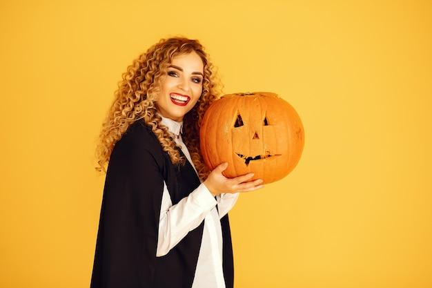 Vrouw draagt zwart kostuum. dame met halloween-make-up. meisje dat zich op een gele achtergrond bevindt. Gratis Foto