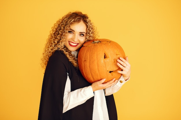 Vrouw draagt zwart kostuum. dame met halloween-make-up. meisje dat zich op een gele achtergrond bevindt.