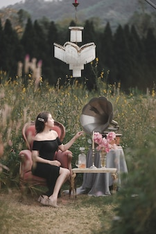 Vrouw draagt zwarte jurk zittend op de bank op bloementuin met vintage grammofoon en decoratie.