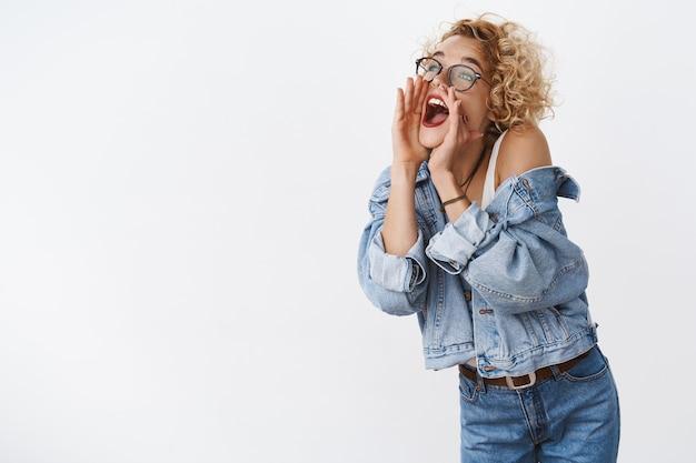 Vrouw draait naar links en schreeuwt terwijl ze om een vriend roept op afstand hand in hand bij geopende mond om stem luider te maken geamuseerd en zorgeloos over witte muur staan schreeuwen iemand zoeken